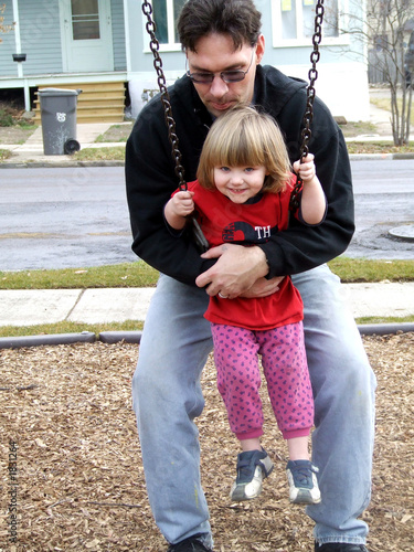 man holding baby on swing