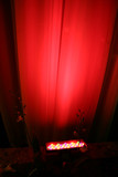 red spot light against curtain poster