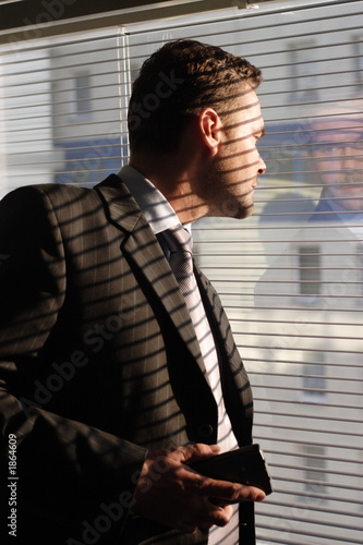 business man with phone  looking through window bl