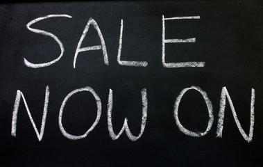 sale now on, written on a blackboard.