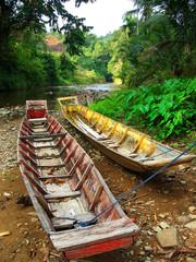 boats beside a borneo river in the jungle