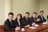 group of 5 business persons sitting at the table poster