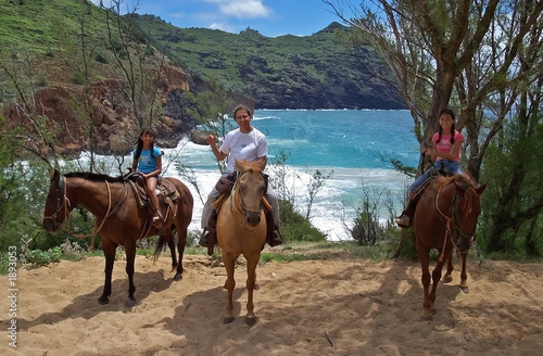 dad with daughters on horseback by a cove