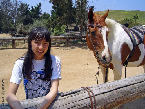 pretty girl standing next to her horse