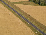 road across field with telegraph pole with automobile. poster
