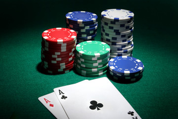 two aces and stack of casino chips in background