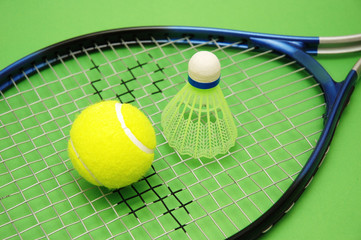 tennis ball, shuttlecock and racket on green backg