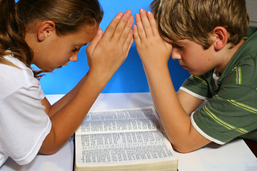 children praying over the bible