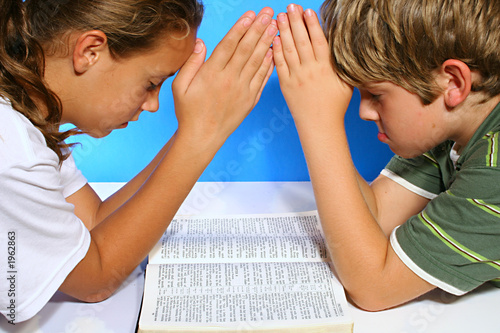 children praying over the bible pout
