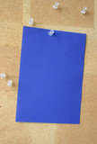 blue paper sheet pinned to corkboard poster