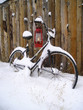 oil lamp and an old bike leaning on a shed in snow