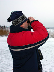 man looking into binoculars
