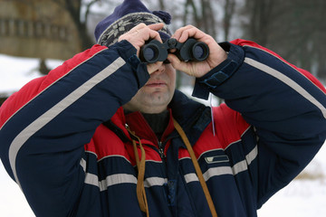 man looking with binoculars