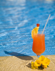orange cocktail stands on edge of pool.