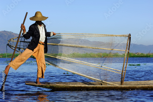 myanmar, inle lake: fishermen on the lake paddling with the help