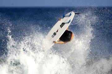 surfer performing a rodeo flip ariel