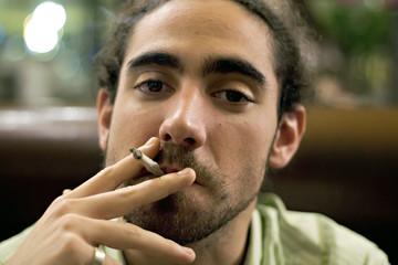 jeune homme fumeur dans un lieu public