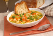 bowl of chicken noodle soup with rustic bread and a glass of win