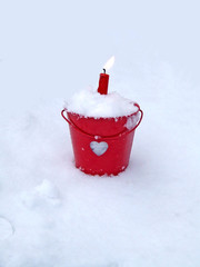 red candle flame in white snow