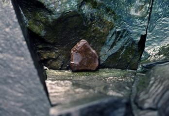 pentagonal ice-covered rock in frozen creek-bed