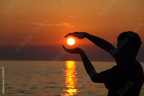 a human trying to hold and protect the sun