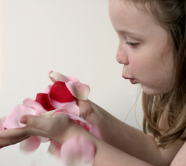 girl blowing rose petals