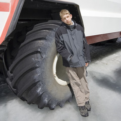 teenage boy in front of a large tire