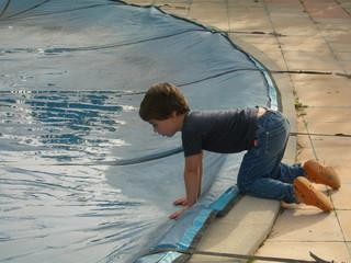 jeune garçon se penchant au dessus d'une piscine