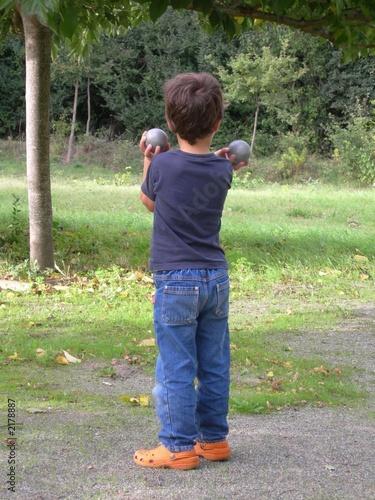 jeune garçon portant des boules de pétanque