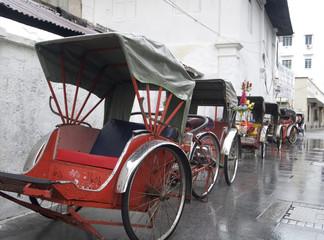 trishaws waiting in the rain