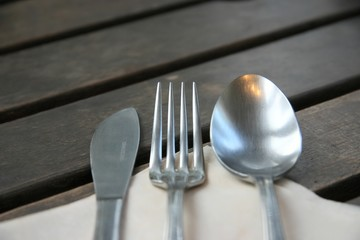 knife, fork, spoon on a wooden table