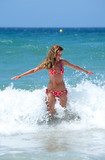 sexy fit young woman being splashed by a wave