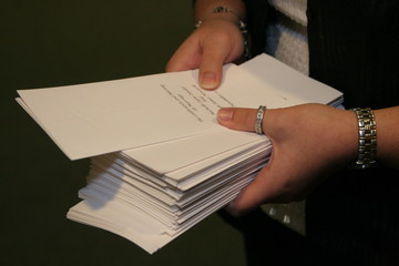 hands holding wedding programs with jewelry