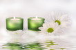 green candles and daisies near water reflection
