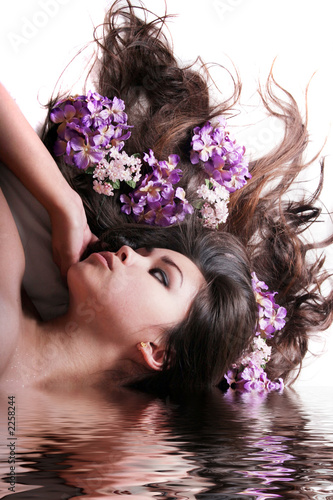 gorgeous long haired woman with flowers in water