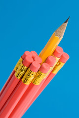 sharp yellow pencil amongst red pencils