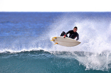 surfer executing an ariel maneuver
