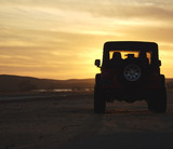 vehicle in the wilderness at sunset poster