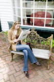 Young blond woman sitting on bench reading newspaper poster