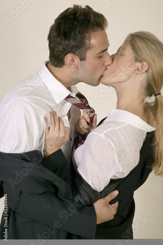 Young couple in business clothes kissing