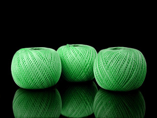 three balls of green string on a black background with reflectio