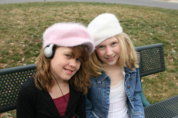 friends listening to music on bench