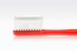 red toothbrush with toothpaste