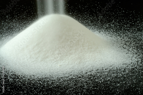 sugar falls on a mountain of granulated sugar on a black backgro