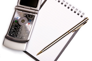 office equipment concept - spiral notebook, pen and modern phone