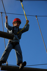 boy takes a risk by standing on a steel wire