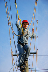 courageous boy standing on a steel wire high above