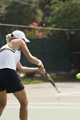 beautiful blonde woman returning tennis serve