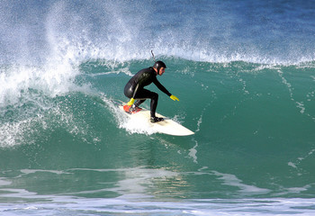 a surfer in trim on a wave