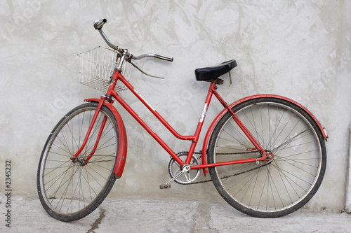 old red bicycle leaning against a wall - 2345232